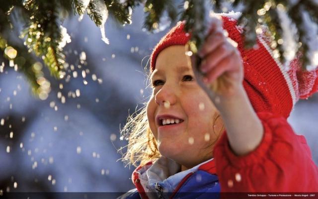 Bambino che gioca con  la neve sui rami