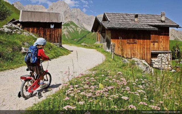 Bambino in bicicletta tra le baite